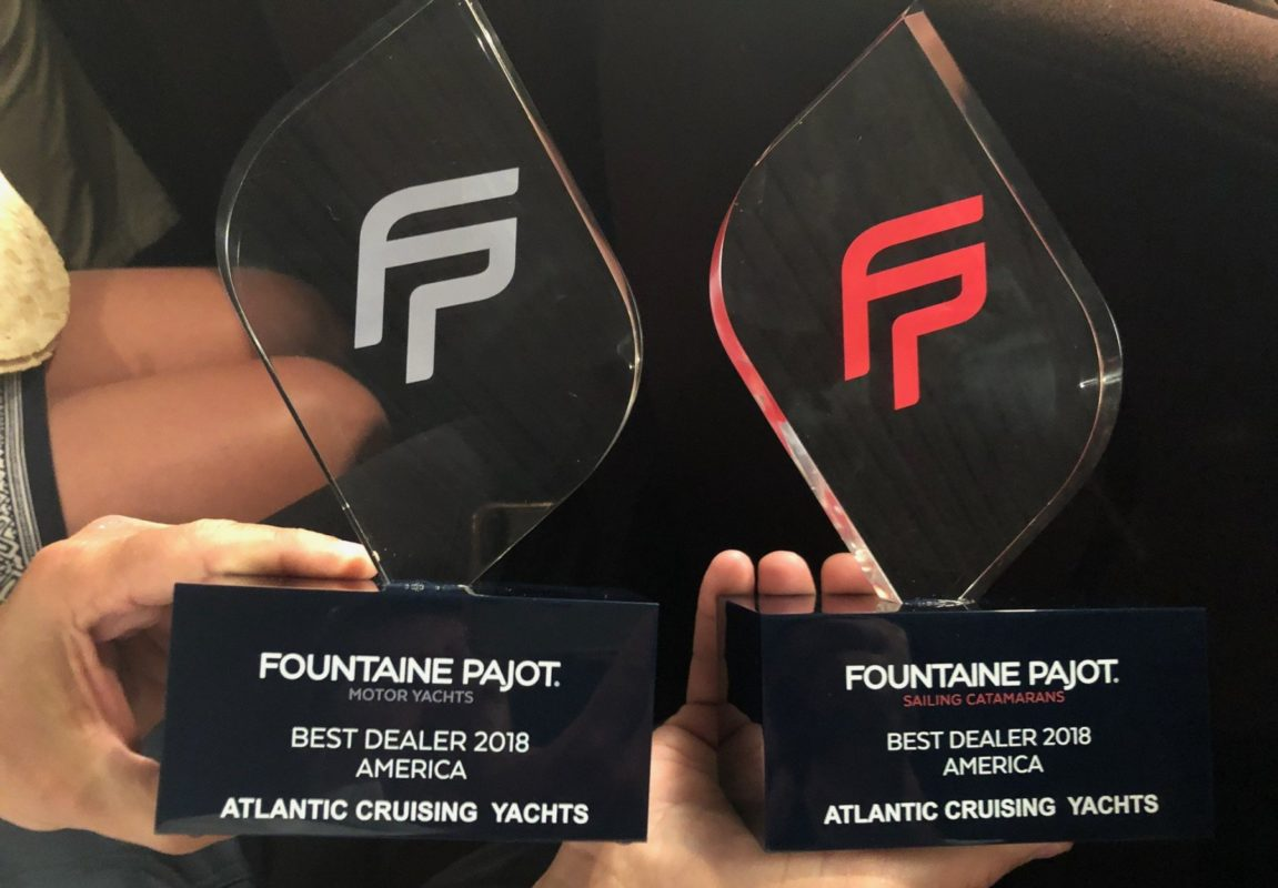 Hands holding two ACY trophies for Fountaine Pajot Best Dealer 2018 America Motor Yachts and Sailing Catamarans