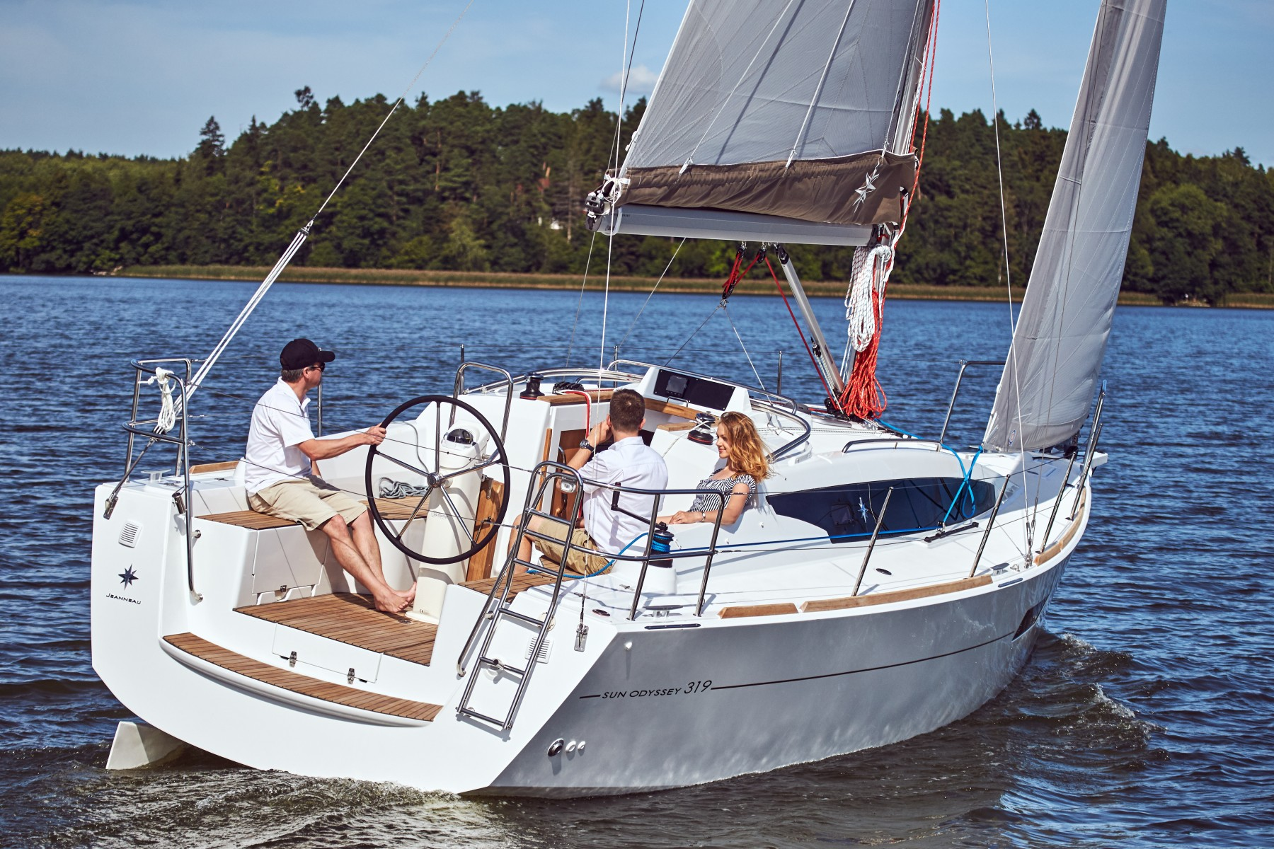Three people on Jeanneau Sun Odyssey 319 while it sails