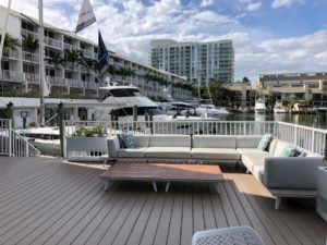 Images of a deck and some couches with yachts in the background