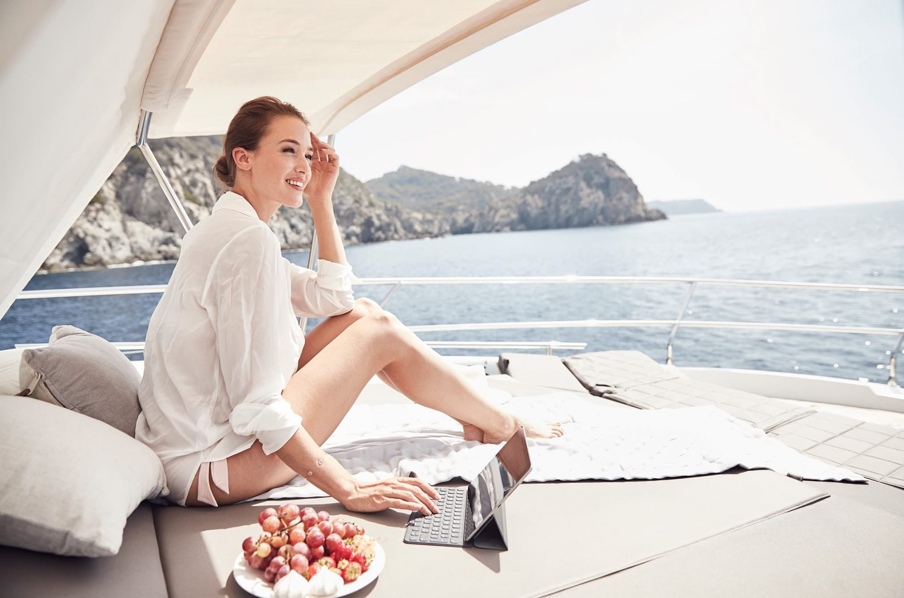 A woman using a tablet on the deck of a yacht