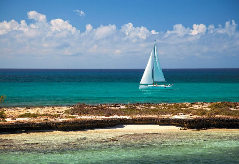 A sailboat anchored near a beach