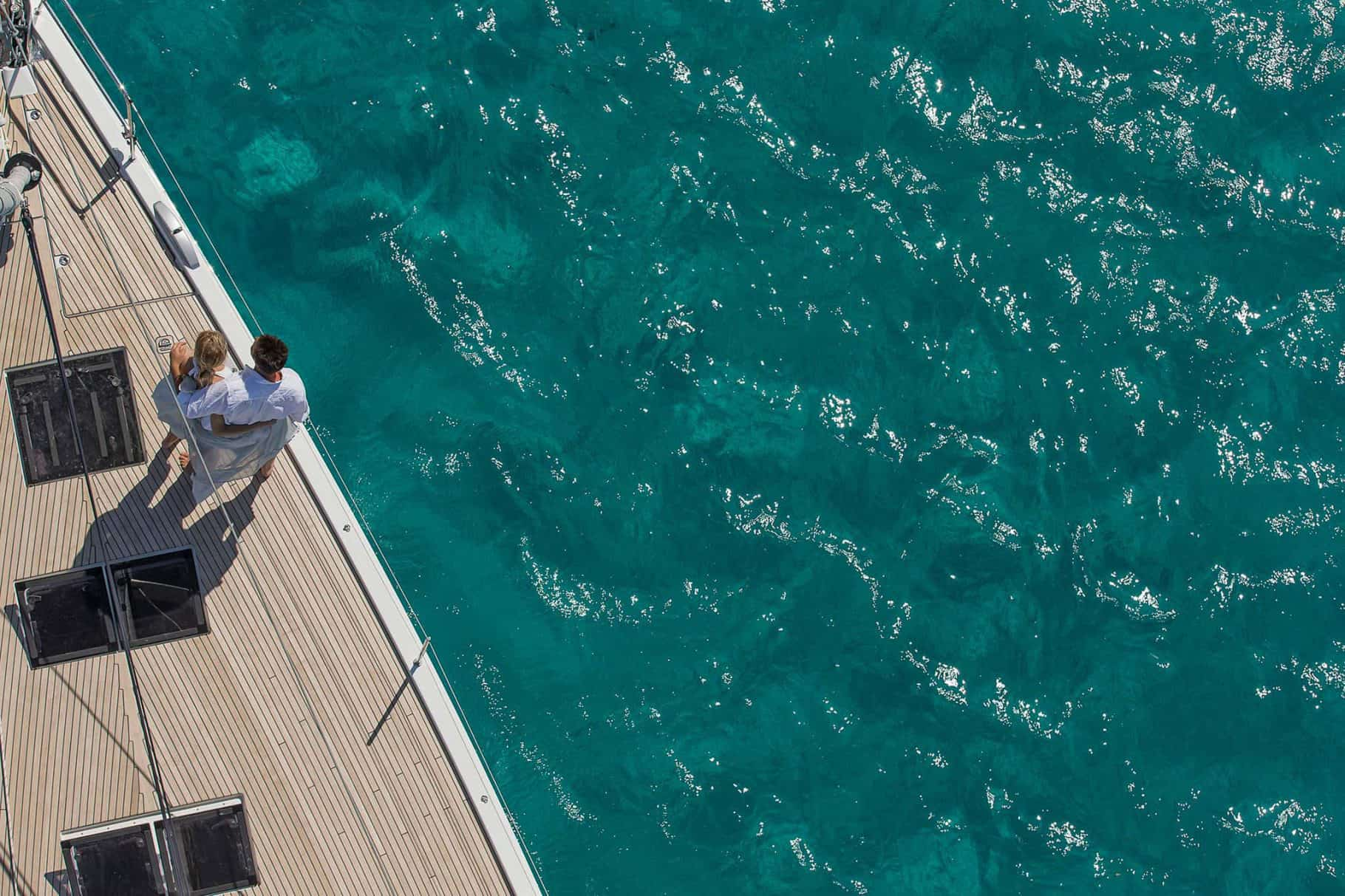A man and woman looking at the ocean from the deck of a yacht