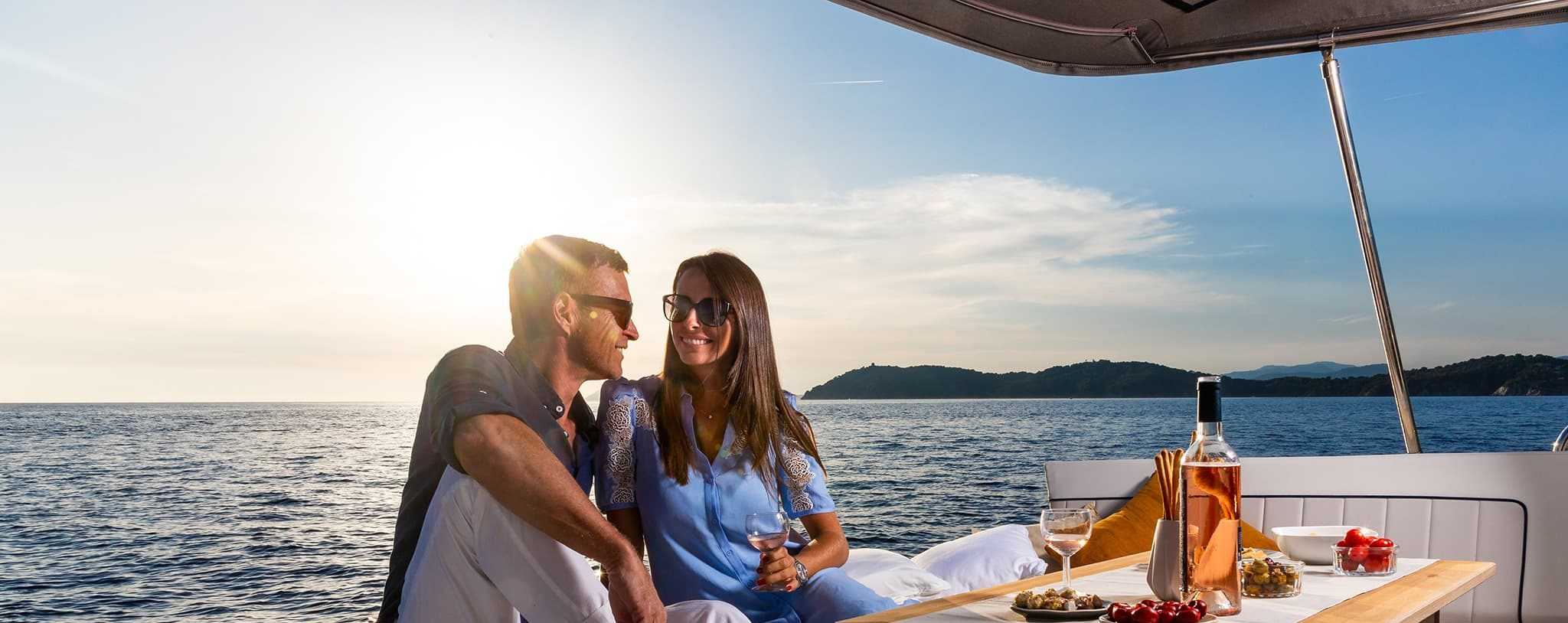 A man and woman enjoying a meal and champagne on the deck of a yacht