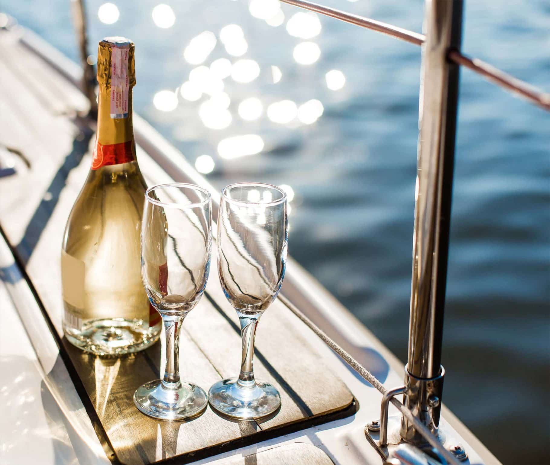 A bottle of champagne and glasses glistening in the sun