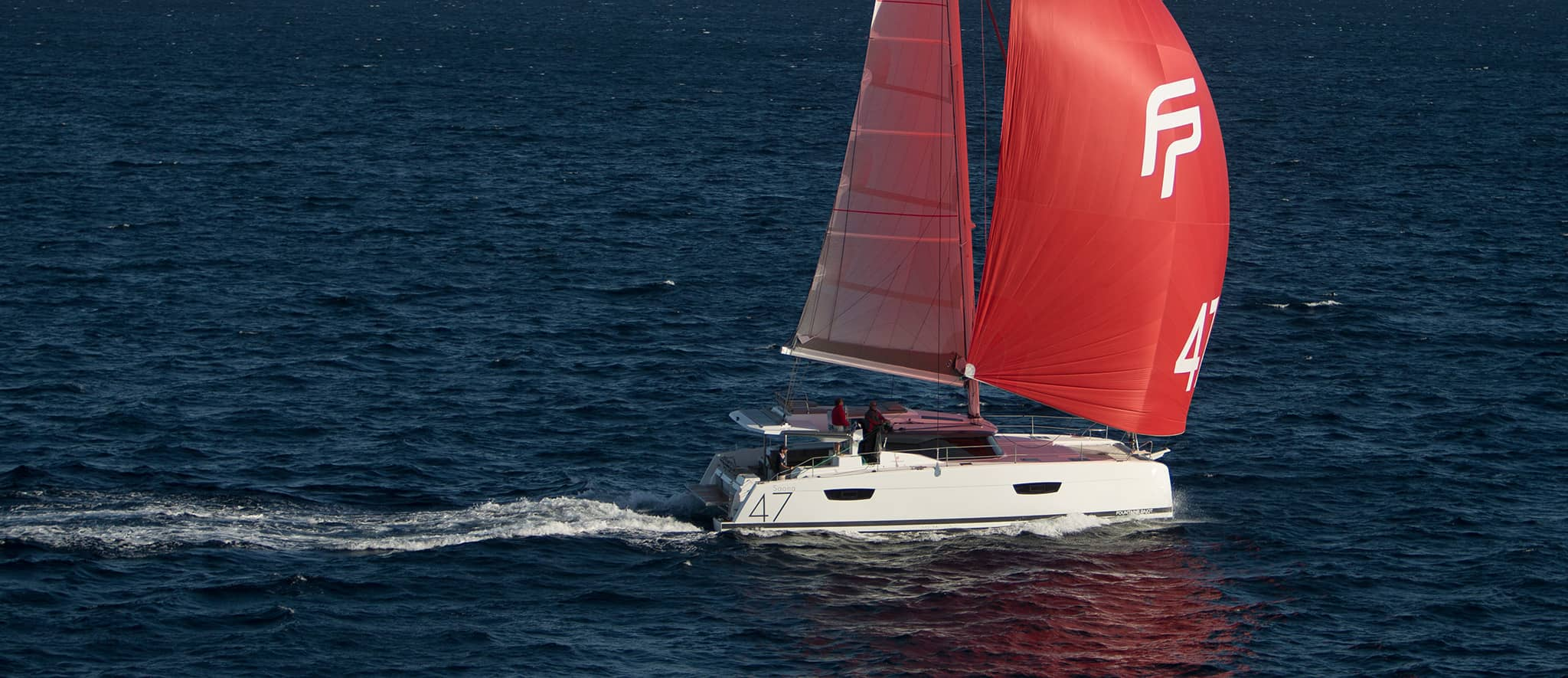 A catamaran sailing on an open body of water on a sunny day