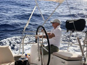 David Dodgen at the helm of a sailing catamaran