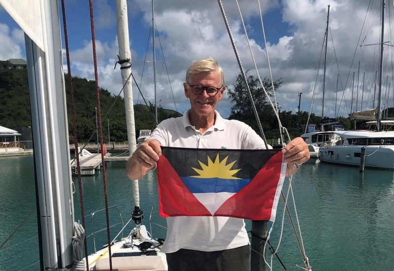 Man holding flag while Sailing the Leeward Islands